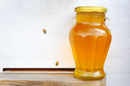 Bottle with honey on beehive background
