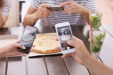 People making photo of pizza
