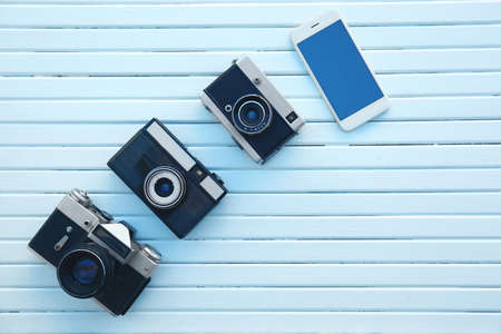 Camera evolution concept. Vintage and modern cameras on white wooden background Stock Photo
