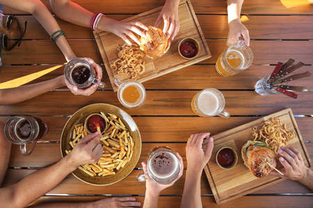 Group of friends drinking beer and eating snacks on wooden background