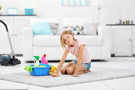 Little girl cleaning floor carpet
