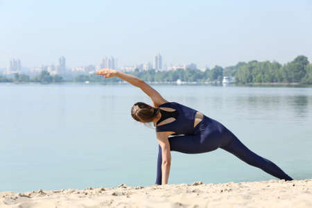 Attractive young woman doing yoga by the river Stock Photo