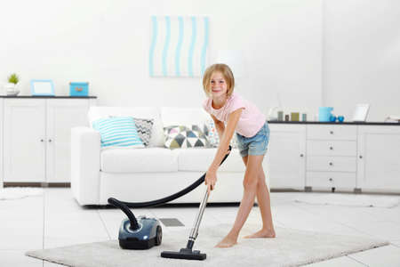 Little girl vacuuming floor with  vacuum
