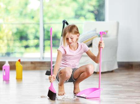 Little girl sweeping floor