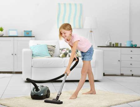 Little girl vacuuming floor with  vacuum