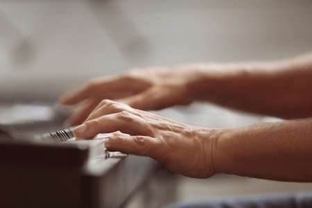 Male hands playing on synthesizer Stock Photo