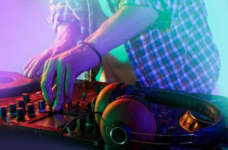 DJ mixing tracks on a mixer in a nightclub