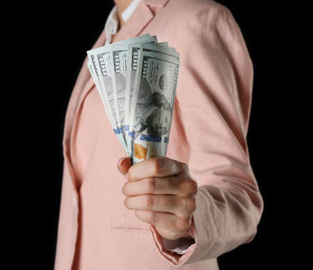 Woman with money on black background Stock Photo