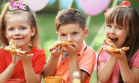 Children eating pizza in park