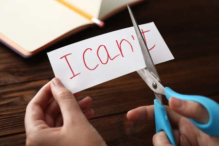 Hand cutting phrase I CANT on wooden background