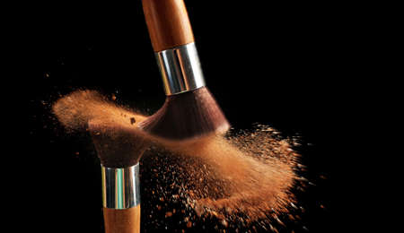 Make-up brush with beige powder explosion on black background Imagens
