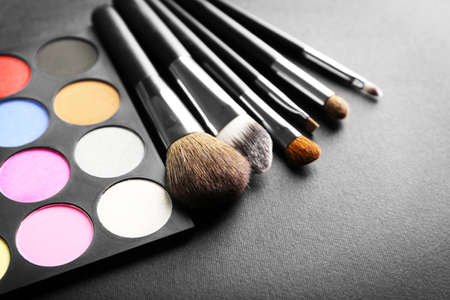 Make up brushes and eye shadow palette on black background