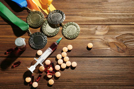 Syringe with pills and medals. Doping in sport concept Imagens