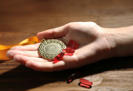 Female hand with pills and medal. Doping in sport concept
