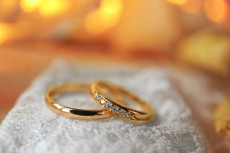 Beautiful wedding rings on white fabric background Stock Photo