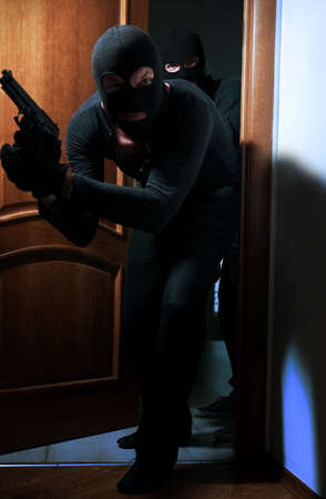 Armed thieves entering a house Stock Photo
