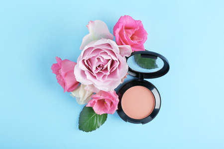 Blusher and flowers on blue background