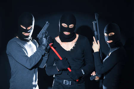 Armed thieves in balaclavas on black background