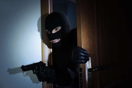 Armed thief entering a house Stock Photo