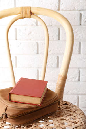 Book with handbag on wicket chair Stock Photo