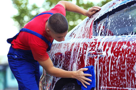Serviceman washing a car