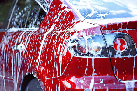 Car washing concept. Red car in foam Stock Photo