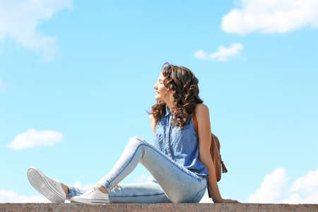Beautiful young girl posing on blue sky background Stockfoto