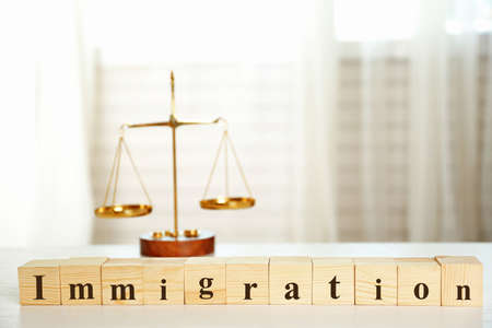 Wooden cubes with word IMMIGRATION and scales on a table