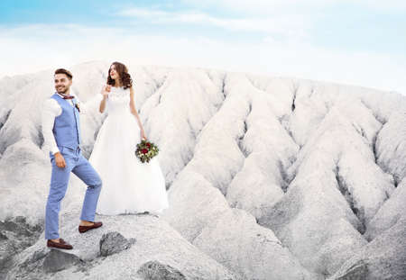 Bride and groom standing over beautiful landscape