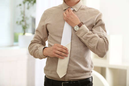 Man adjusting leather tie in office
