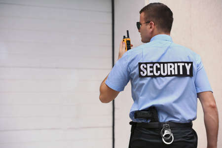 Male security guard with portable radio outdoors Banque d'images