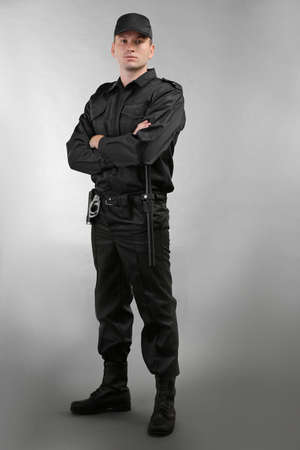 Male security guard on grey background Standard-Bild