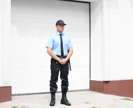 Male security guard beside garage Stock Photo