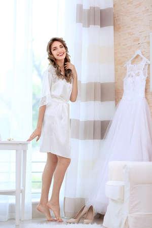 Young beautiful bride with wedding dress in bedroom Standard-Bild