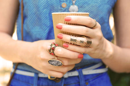 Close up of female hands with beautiful bijouteries holding cup of coffee