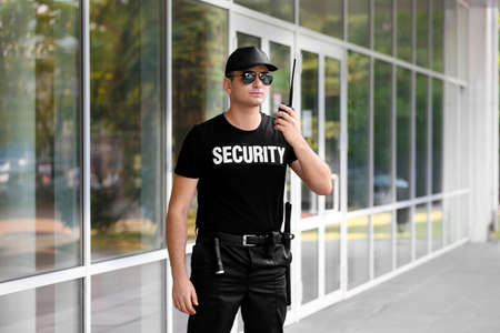 Male security guard with portable radio outdoors 스톡 콘텐츠