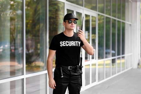 Male security guard with portable radio outdoors Foto de archivo