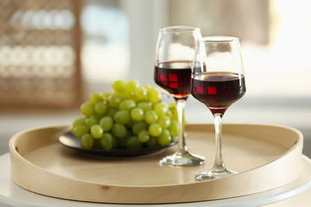 Glasses with red wine and grape on a tray