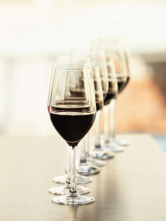 Glasses with red wine in a row on a table Stock Photo