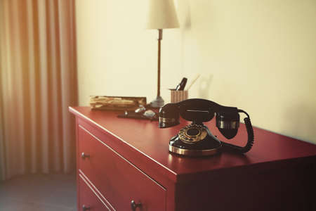 Old telephone on the chest in bedroom Stock Photo