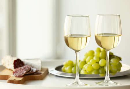 Glasses with white wine and grape on a table Stock Photo