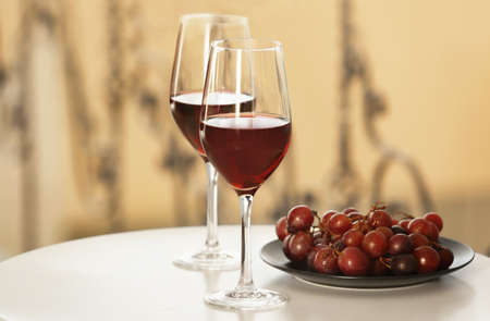 Glasses with red wine and grape on white table