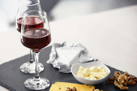 Glasses with red wine and tasty cheese on a board