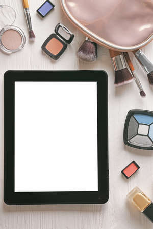 Tablet and cosmetics on wooden background Stock Photo
