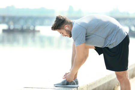 Sporty man tying shoelaces outdoors