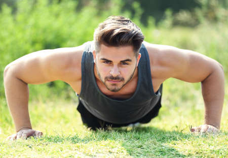 Young man making push-ups outdoors Stock Photo