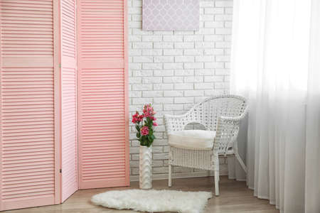Light room interior with pink folding screen Фото со стока