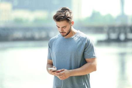 Sporty man listening music outdoors