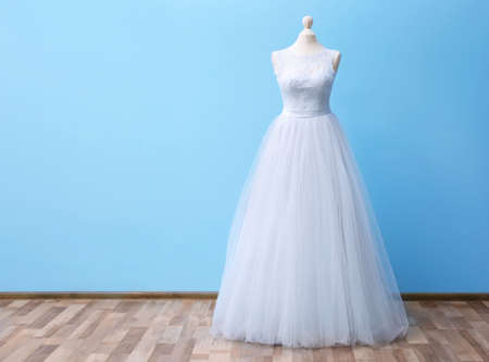 Beautiful wedding dress on floor beside blue wall background Stock Photo