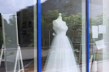 Beautiful wedding dress behind shop window